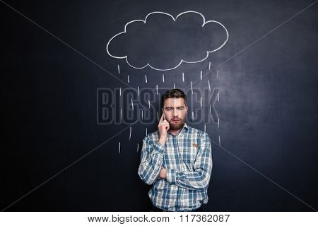 Sad handsome young man with beard talking on mobile phone  under raincloud and rain drawn over him on a blackboard background