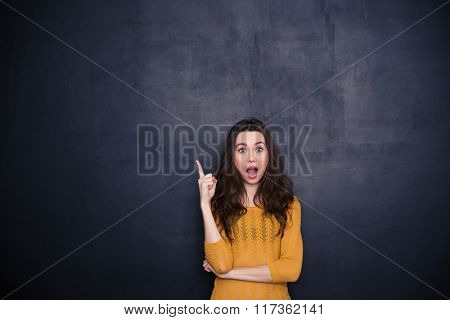 Amazed woman pointing finger up over black background