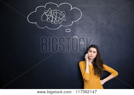 Unhappy pretty young woman talking on cell phone standing over background of chalkboard