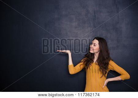 Happy woman holding copyspace on the palm over black background