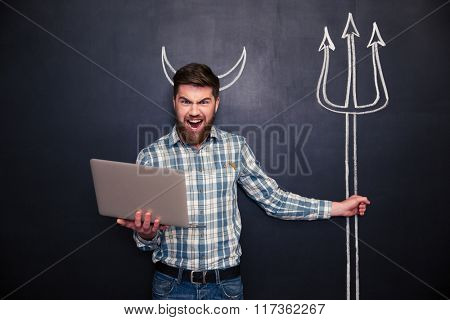 Angry bearded man using laptop and holding trident drawn on blackboard background