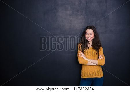 Smiling casual woman standing with arms folded over black background