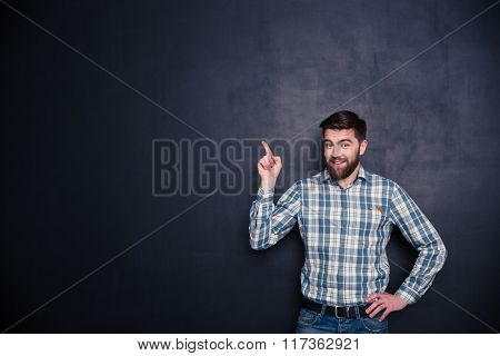 Happy man pointing finger at copyspace over black background