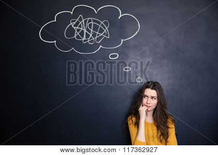 Frowning thougthful young woman thinking about problems over blackboard background