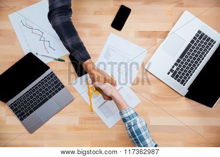 Top view of african and caucasian men shaking hands after working with reports on laptops