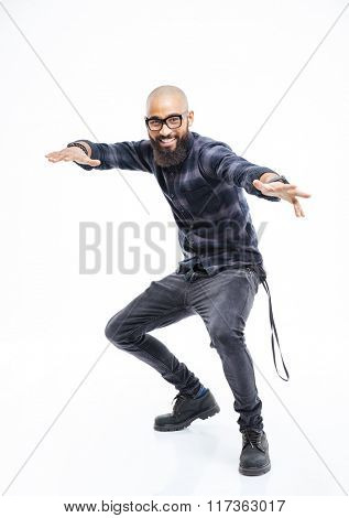 Happy african american young bearded man in glasses balancing and dancing