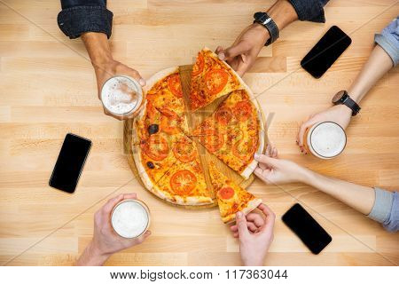 Group of young friends tasting pizza and drinking beer on wooden table
