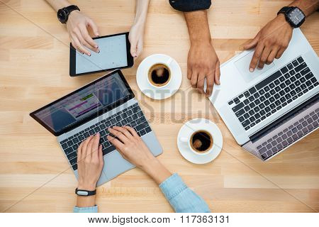 Top view of multiethnic group of young people using laptops and tablet and drinking coffee