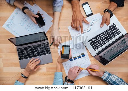 Top view of group of business people using cell phones and laptops and working for a financial report