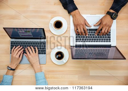 Top view of hands of man and woman working with two laptops and drinking coffee on wooden table