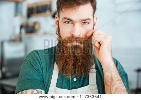 Closeup portrait of handsome young man with beard in white apron touching his moustache