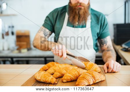 Young man barista with beard and tattooed hands taking croissant using tongs in coffee shop