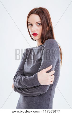 Fashion portrait of beautiful young woman with red lips standing with hands folded over white background