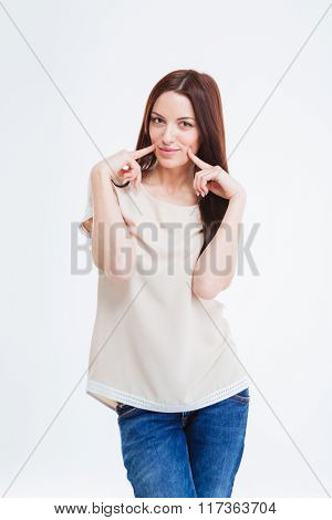 Cute lovely youn woman in blouse and jeans standing and touching her cheeks over white background