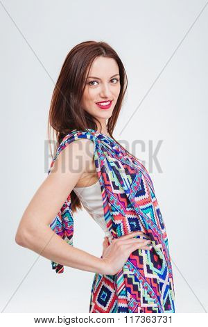 Beautiful smiling young woman in colorful sundress posing over white background