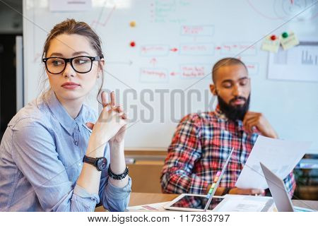 Pensive young woman in glasses sitting in conference room and thinking while her male colleague reading