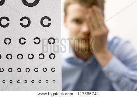 Eyesight Check. Male Patient Under Eye Vision Examination. Focus On Test Chart
