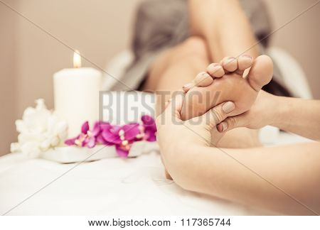 Close Up Of Woman's Feet And Beauty Saloon Decorations