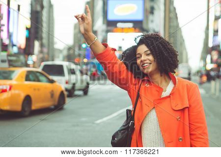 Woman calling a taxi in Time square