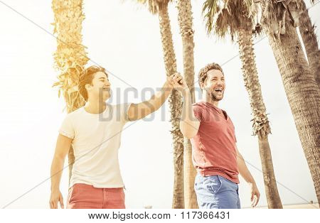 Happy Male Couple In Love Playing In Santa Monica On The Beach