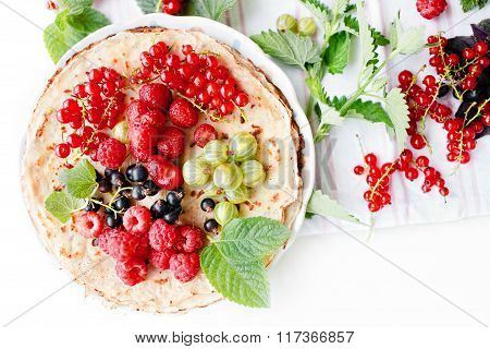 Traditional thin russian pancakes with season berries and mint
