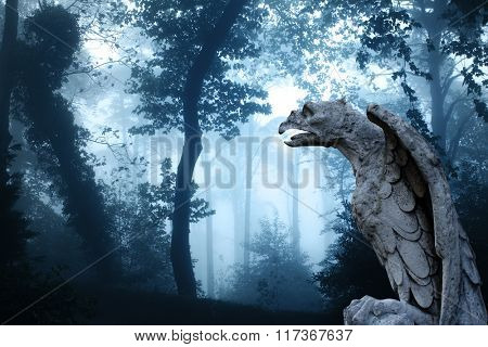 Ancient eagle statue and mysterious landscape of foggy forest