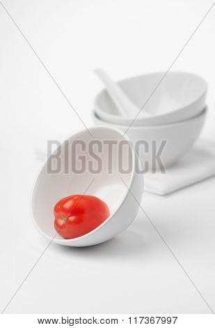 Whole red tomato in a bowl. Modern and minimal food styling.
