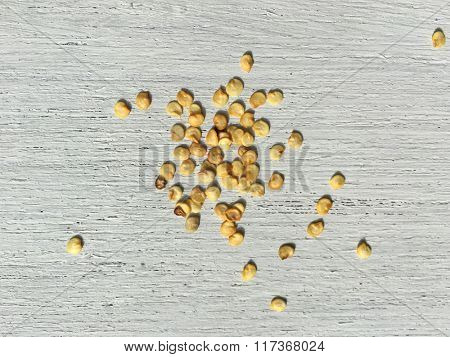 Few scattered red chili seeds on white background.