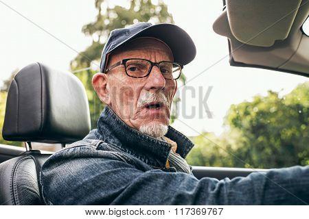 Man Driving Car Looking At Camera.
