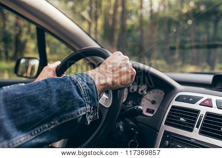 Hands Of Man On Steering Wheel Of Car. Interior Shot.