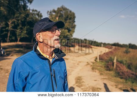 Active Senior Man Enjoying View Of Heathland.