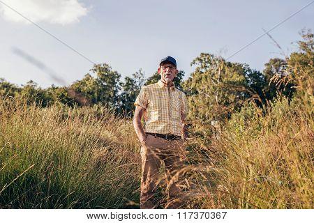 Senior Man Standing Between High Grass In Park.