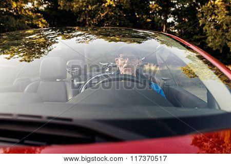 Senior Man Sitting In Sports Car Outdoors In Park.