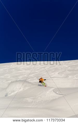 Male Skier Skiing In Fresh Snow On Ski Slope On A Sunny Winter Day