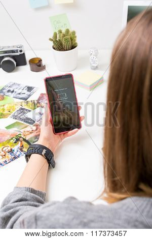 Young woman with smartphone with empty battery