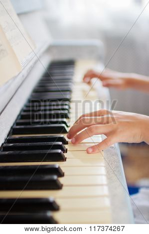 hands of a young girl playing the piano