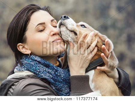 Woman tenderly hugs her beagle while walking outside