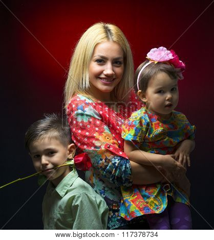 Mother With Her Two Children Isolated On Black Background