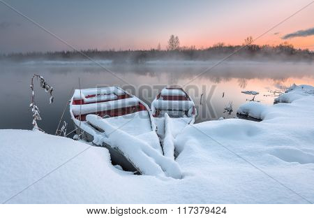 The boats in the winter on the freezing lake