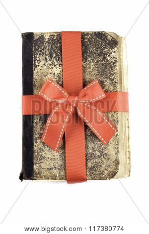 old book as a gift with red ribbon isolated