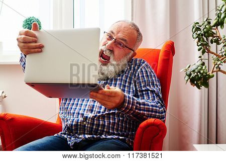 mad senior man sitting on the chair and screaming at laptop at home