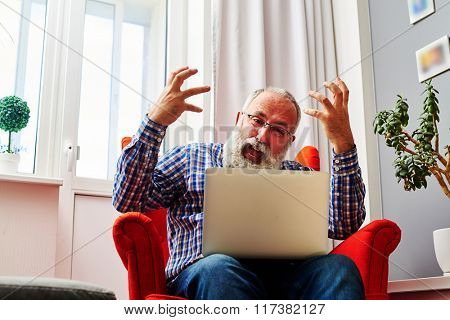 emotional senior man waving his arms and shouting at a laptop at home