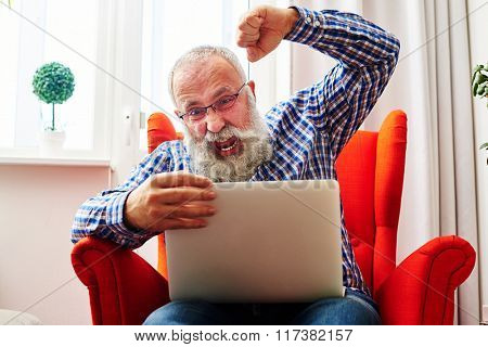 emotional senior man brandishing his fist and screaming at laptop at home