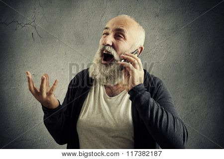 emotional senior man talking on the phone and laughing over dark background