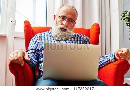 sad senior man sitting on the chair and looking at laptop