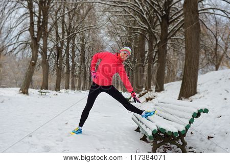 Winter running in park: happy woman runner warming up and exercising before jogging in snow