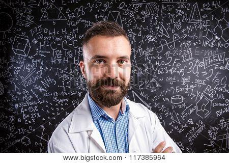 Teacher in white coat against big blackboard with mathematical s