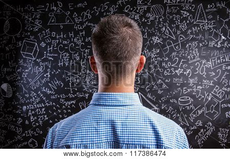 Back view of teacher against big blackboard with mathematical sy