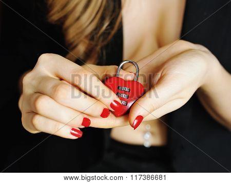 Padlock red heart-shape in a women's hands