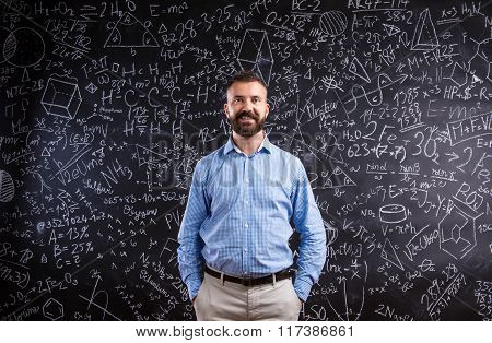 Hipster teacher against big blackboard with mathematical symbols